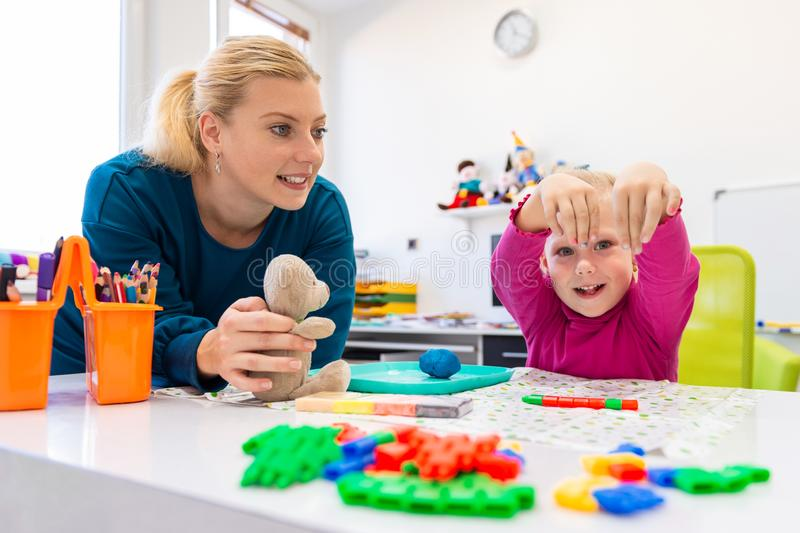 Toddler girl in child occupational therapy session doing sensory playful exercises with her therapist. Toddler girl in child occupational therapy session doing royalty free stock images