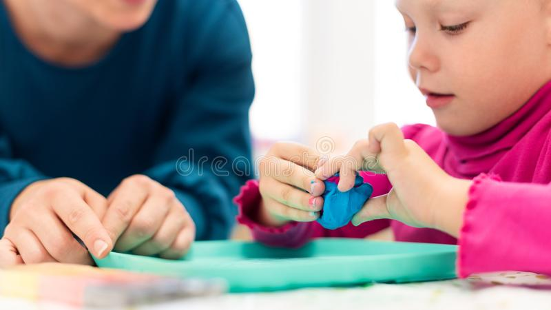 Toddler girl in child occupational therapy session doing sensory playful exercises with her therapist. Toddler girl in child occupational therapy session doing stock photo