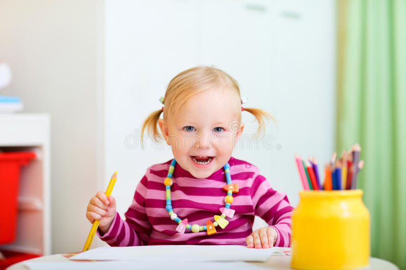 Toddler girl drawing with pencils stock image