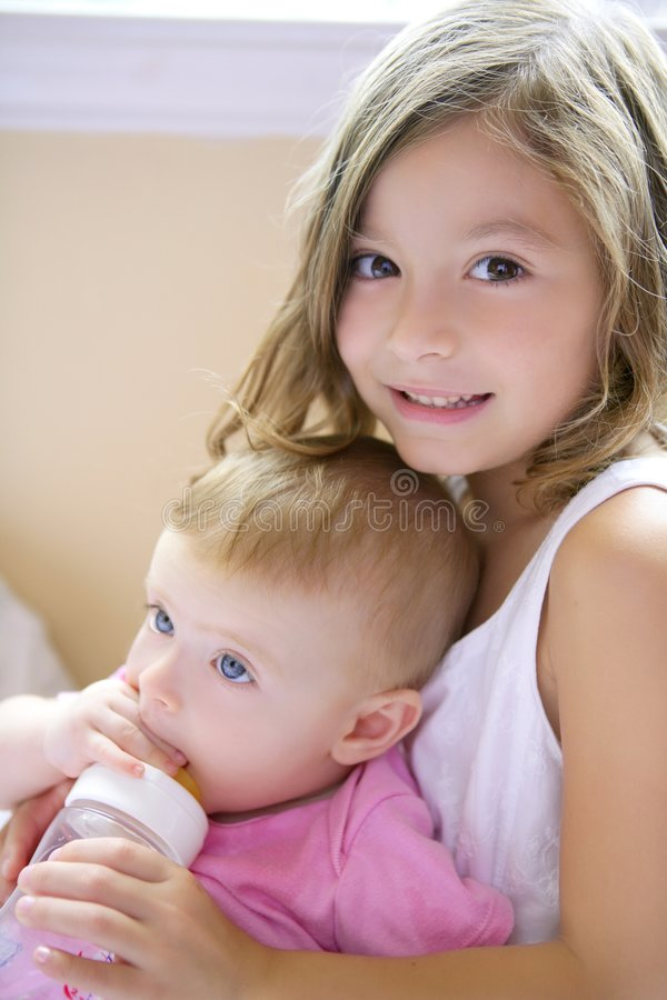 Toddler girl giving bottle of milk to baby sister royalty free stock photo