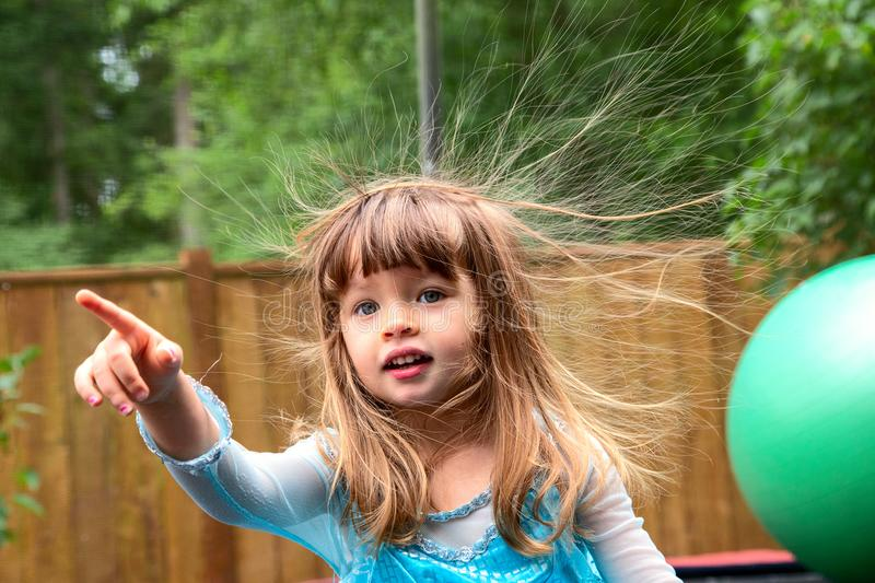 Toddler girl having a bad hair day. Toddler girl pointing her finger and looking like she`s having a bad hair day after playing on the trampoline stock photos