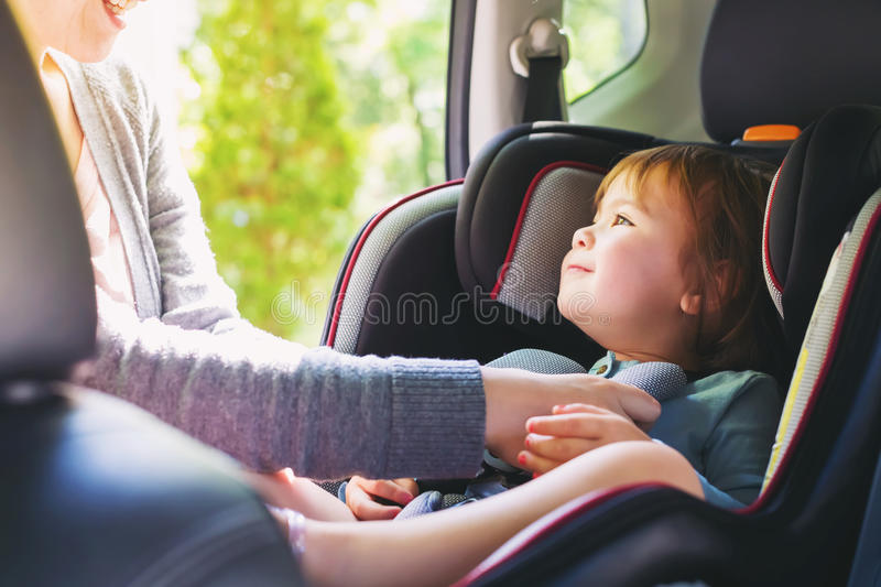 Toddler girl in her car seat. Toddler girl buckled into her car seat stock image