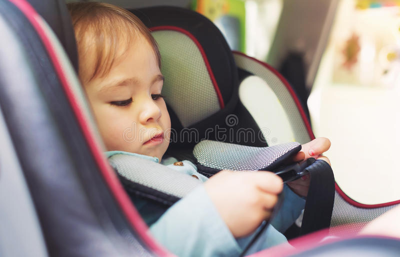 Toddler girl in her car seat. Toddler girl buckled into her car seat royalty free stock photography