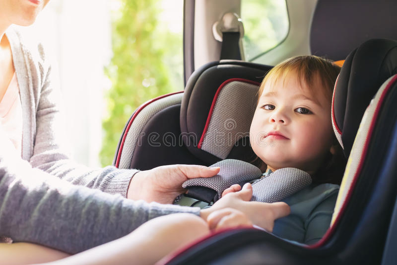 Toddler girl in her car seat. Toddler girl buckled into her car seat royalty free stock image