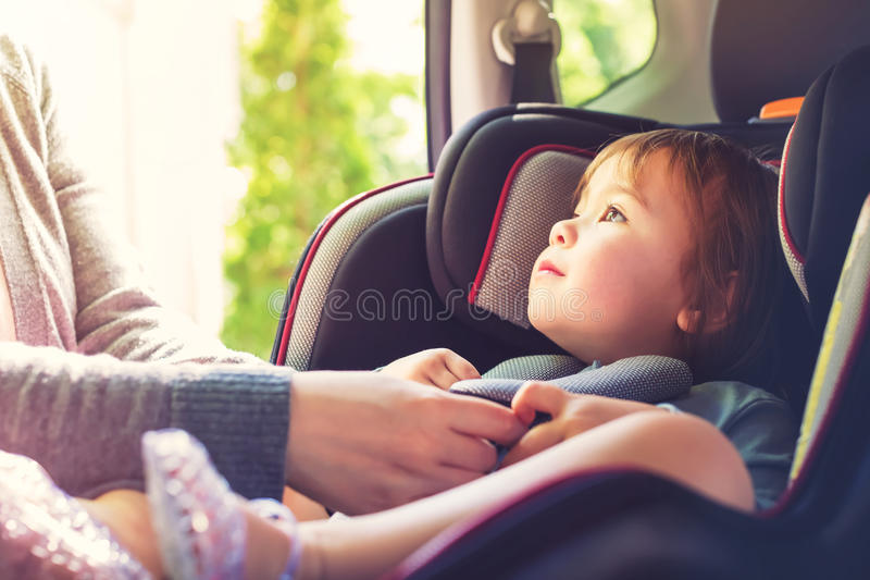 Toddler girl in her car seat. Toddler girl buckled into her car seat royalty free stock images