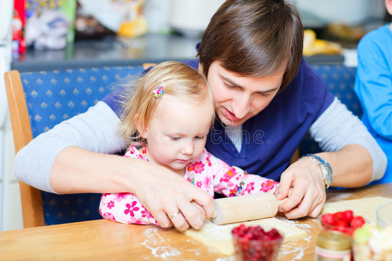 Toddler girl and her dad baking pie. Adorable toddler girl at kitchen baking pie together with her father stock photography