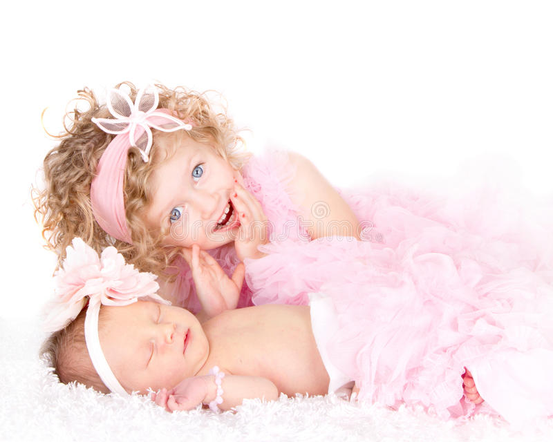 A toddler girl with her infant sister. A cute blue eyed toddler girl with her sleeping infant sister royalty free stock photography