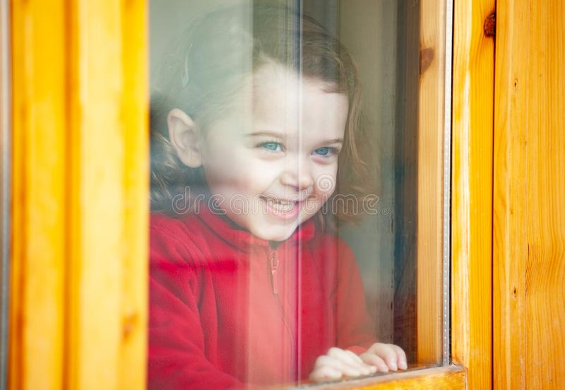 Toddler girl looking out of the window stock images