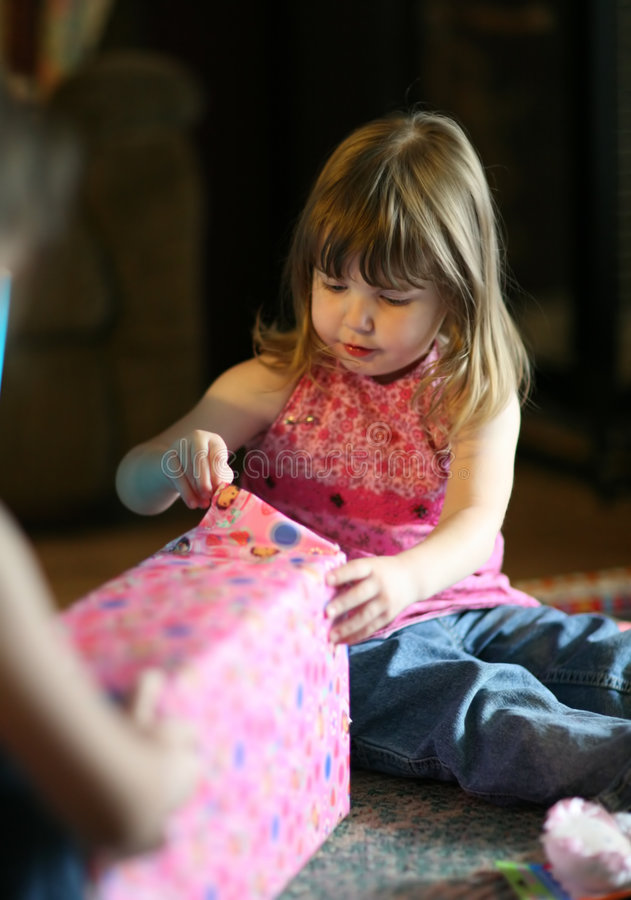 Toddler Girl Opening Birthday Gifts. Young Child Opening Birthday Present royalty free stock photos
