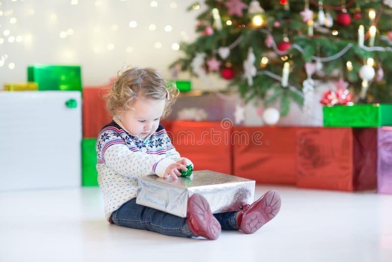 Toddler girl opening her Christmas present under Christmas tree stock image