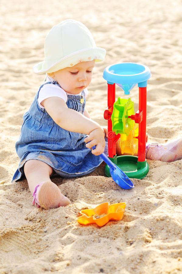Toddler girl playing  toys in sand royalty free stock photo