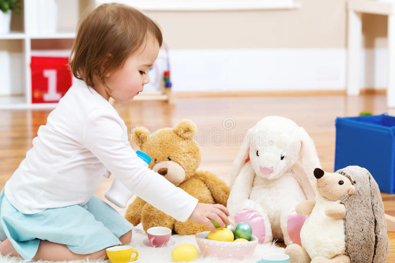 Toddler girl playing with her stuffed animals. In her house royalty free stock photos