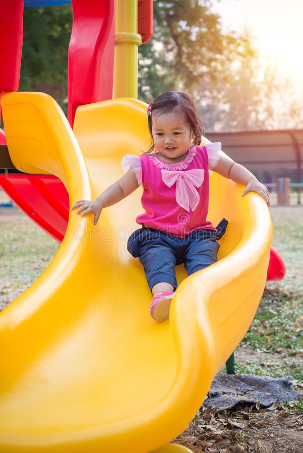 Toddler girl playing on a slide at children playground royalty free stock photo