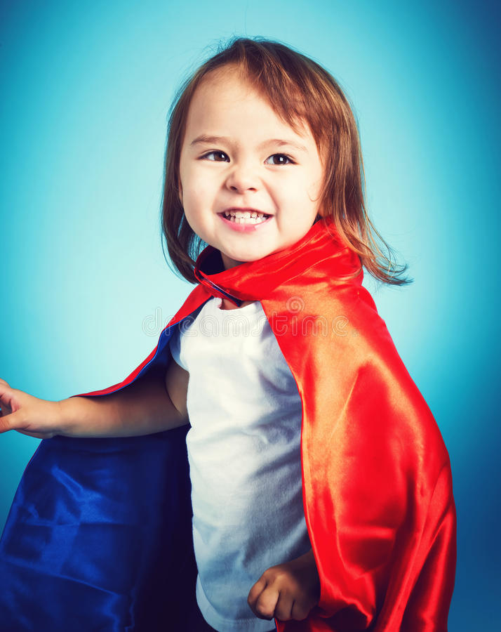 Toddler girl playing in a super hero cape. Happy toddler girl playing in a super hero cape royalty free stock photo