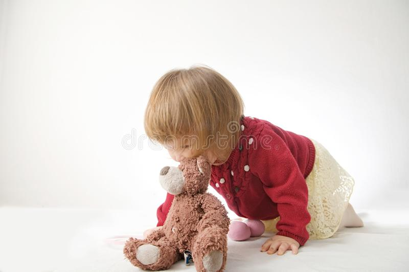 Toddler girl playing with teddy bear like animal stock photo
