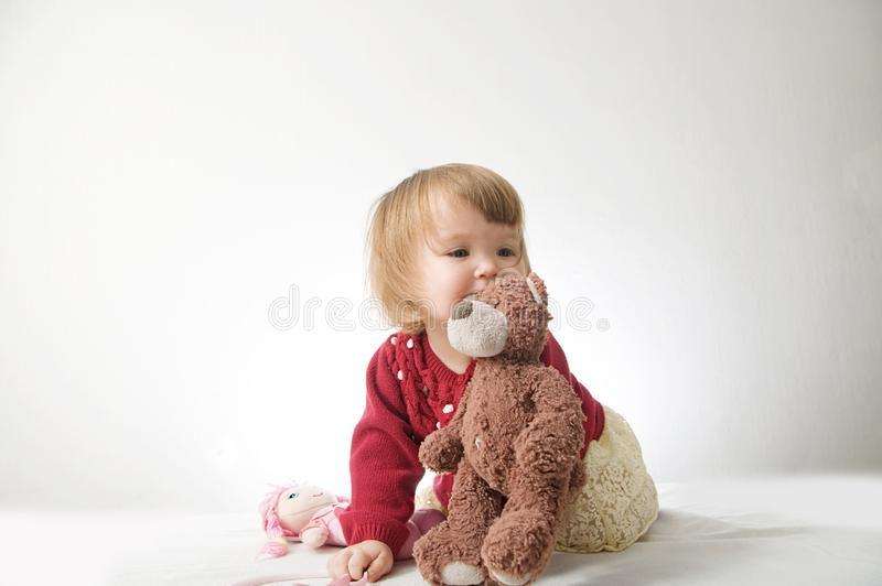 Toddler girl playing with teddy bear like animal stock images