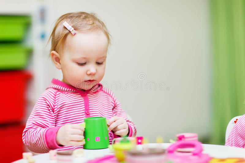 Toddler girl playing with toys. Adorable toddler girl playing with toys at home or daycare place royalty free stock photos