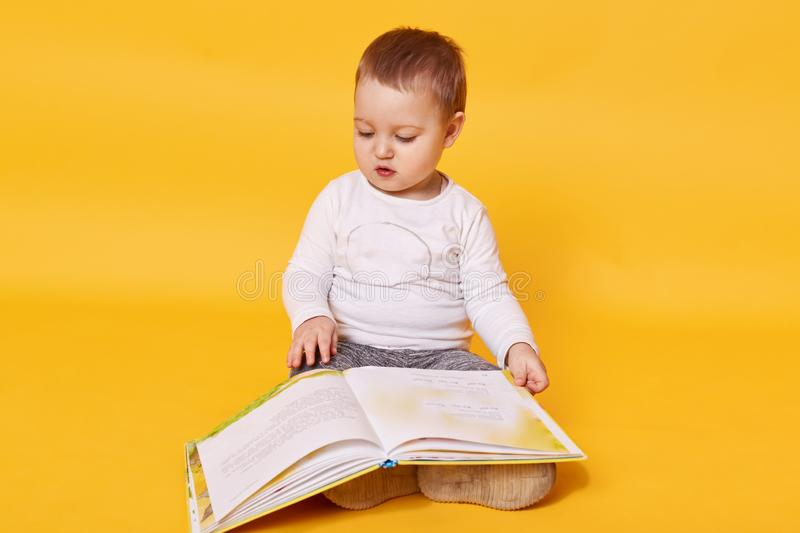 Toddler girl pretends to read book while sitting on floor, viewing pictures and turning pages, little girl looks concentrated,. Wearing casual white shirt stock photos