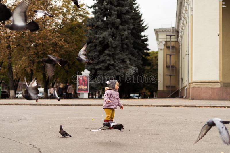 Toddler girl in rain boots playing with birds on city square. Outdoors childhood activity stock photos