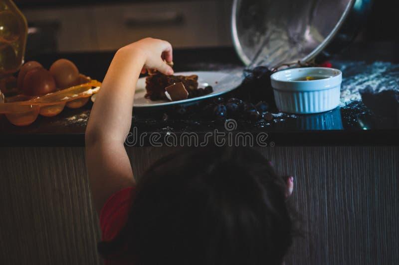 Toddler girl sneaking around grabbing chocolate cake royalty free stock images
