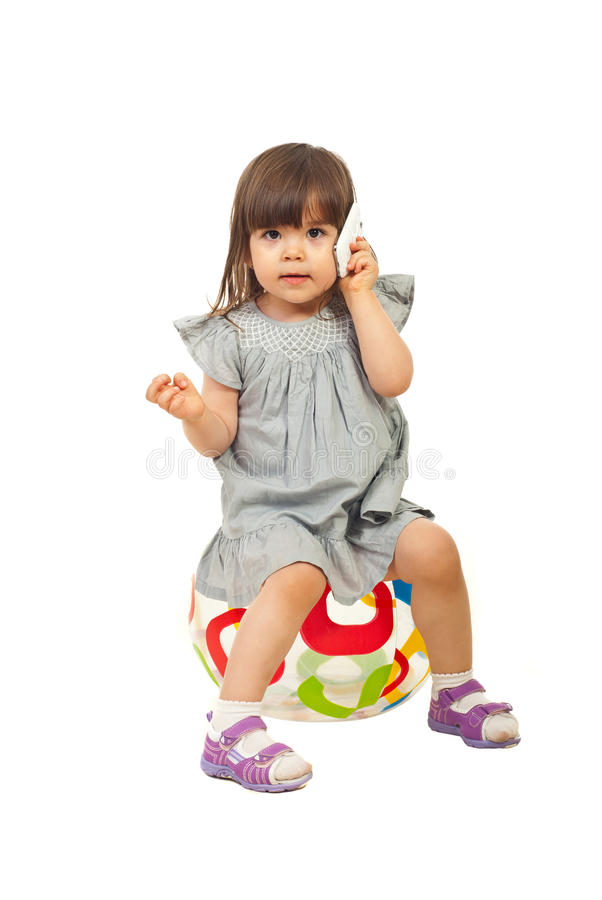 Toddler girl speaking by cell phone stock photography