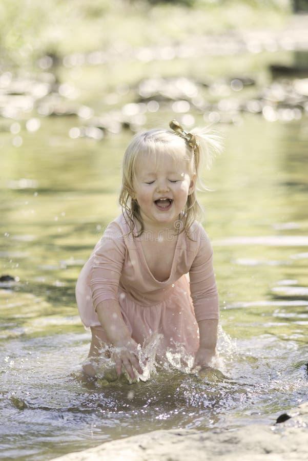 Toddler Girl splashing in the creek royalty free stock photos