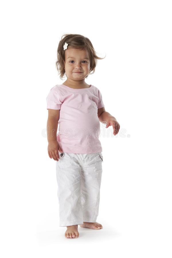 Toddler girl standing and looking into the camera royalty free stock photo