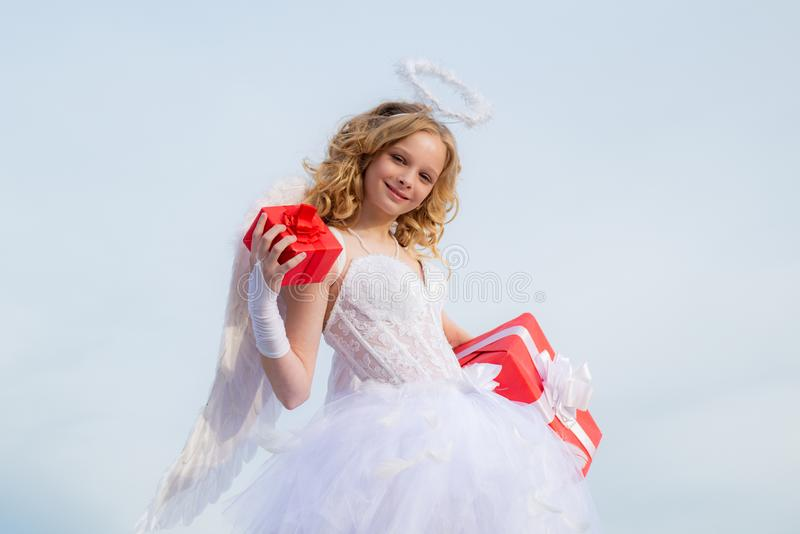 Toddler girl wearing angel costume white dress and feather wings. Cute little Cupid angel with gift. Festive Art stock image