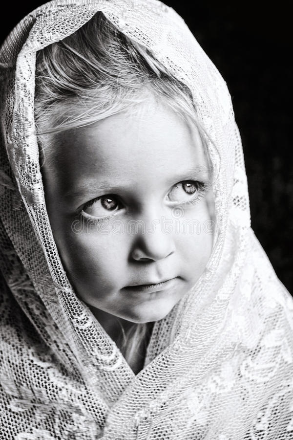 Toddler girl in white lace. Black and white close up portrait of blond toddler girl wrapped in white lace