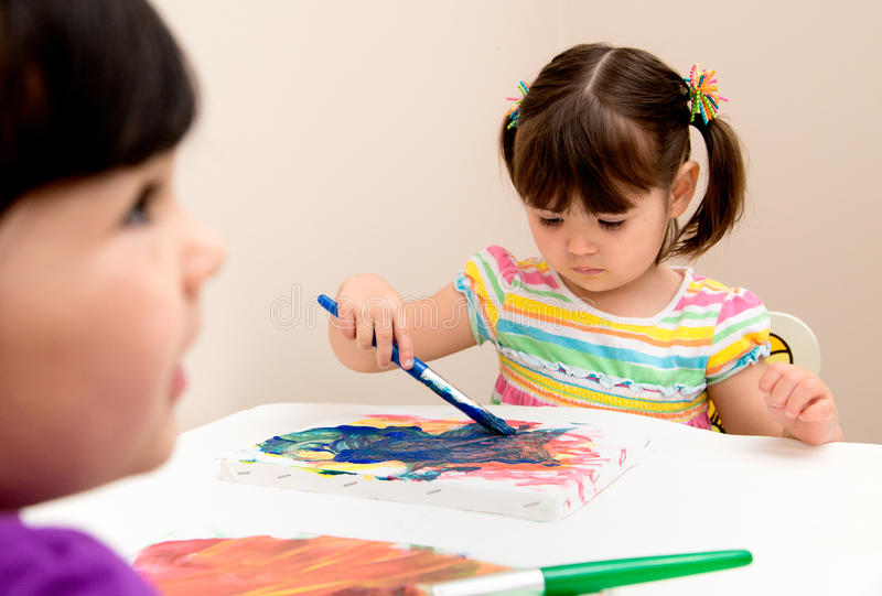 Toddler girls painting in art class. Serious young artist focused on her painting as her sister watches stock images