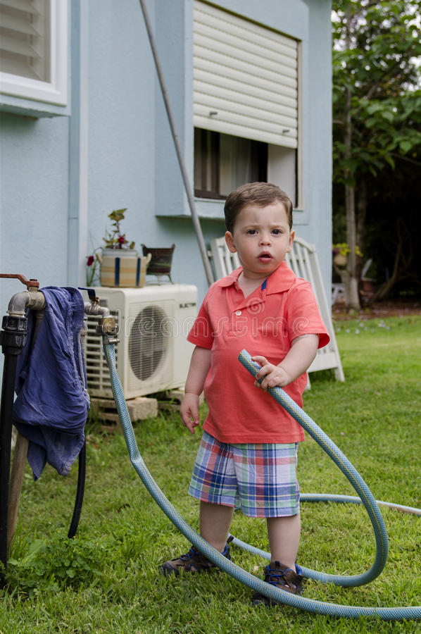 Toddler holding a hose royalty free stock photo