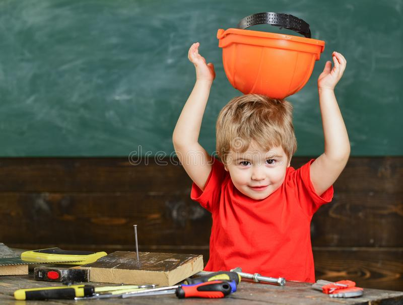 Toddler holds protective hard hat, helmet by wrong side, chalkboard background. Child cute and adorable putting hard hat stock photos