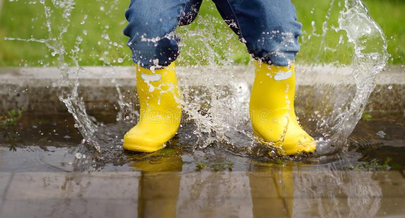 Toddler jumping in pool of water at the summer or autumn day. Outdoors activity for kids royalty free stock images