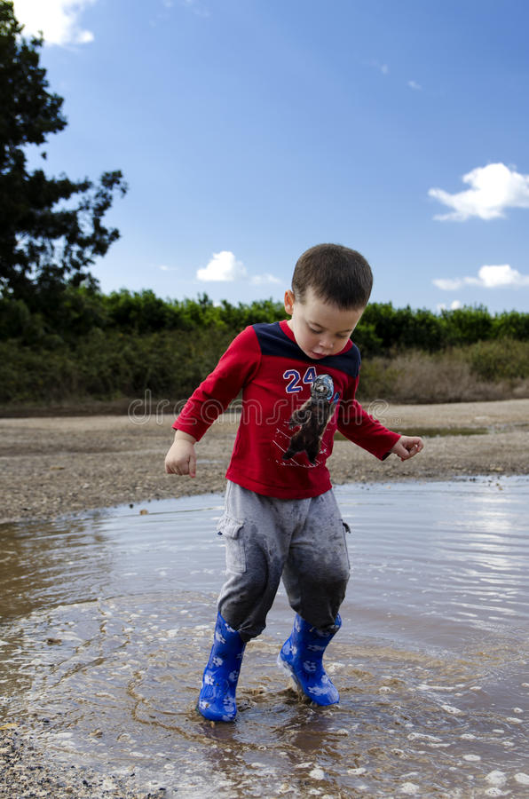 Toddler jumping in a puddle with his new boots royalty free stock images