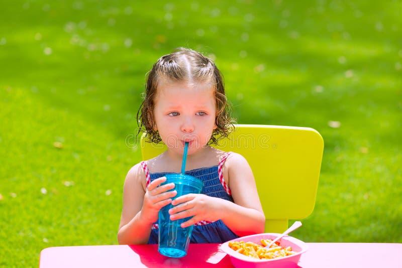 Toddler kid girl drinking eating pasta in garden stock images