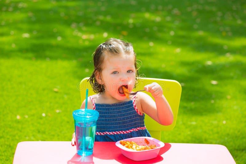 Toddler kid girl eating macaroni tomato pasta. In garden turf grass royalty free stock images