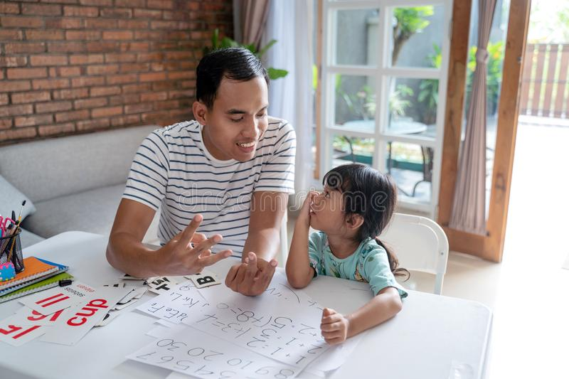 Toddler learning math and counting with her father royalty free stock photography
