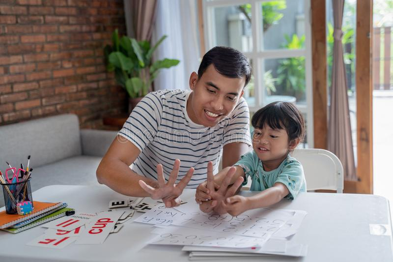 Toddler learning math and counting with her father royalty free stock image