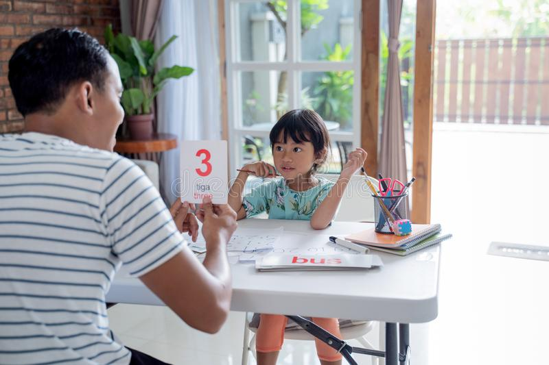 Toddler learning simple math using flash card at home stock image