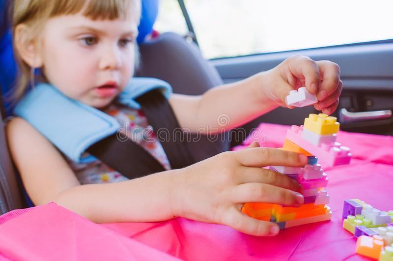 Toddler little girl playing with constructor in the car seat royalty free stock photo