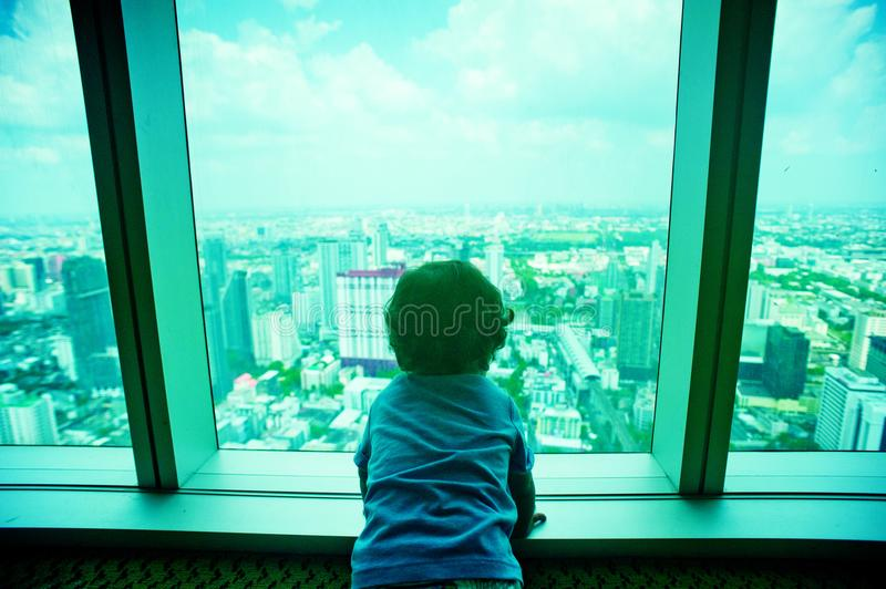 Toddler Looking Through Clear Glass Window stock photography