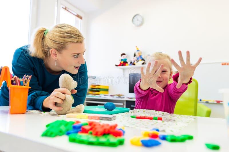 Toddler menina em sessão de terapia infantil em exercício sensorial com seu terapeuta imagem de stock