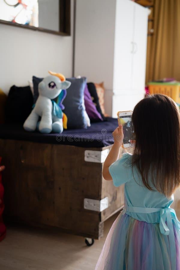 Toddler neemt foto van haar pluchen speelgoed met de mobiele telefoon Kid met technologie royalty-vrije stock afbeeldingen