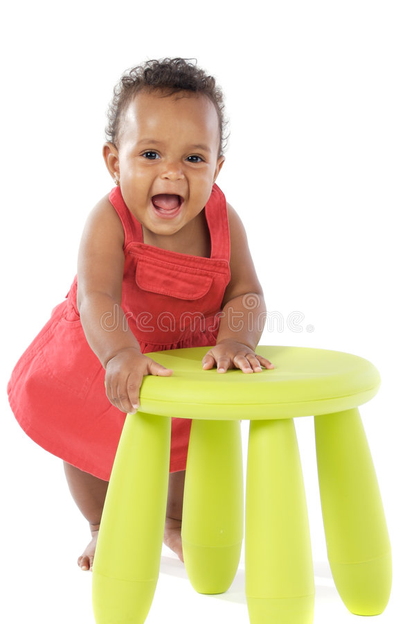 Toddler playing with a chair royalty free stock image