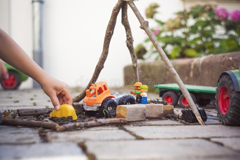 Toddler playing with construction toys in the backyard on a blurred background. A toddler playing with construction toys in the backyard on a blurred background stock images