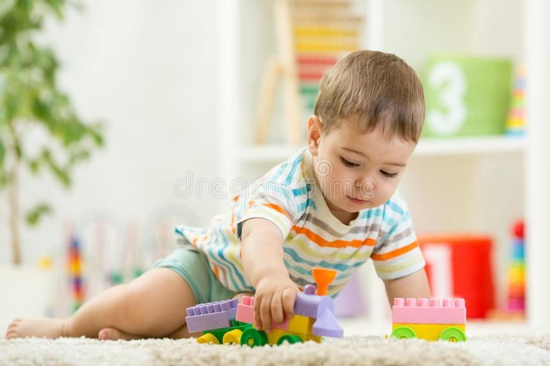Toddler playing with toys on a white carpet at home royalty free stock images