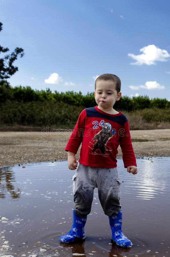 Toddler posing in a puddle with his new boots royalty free stock image