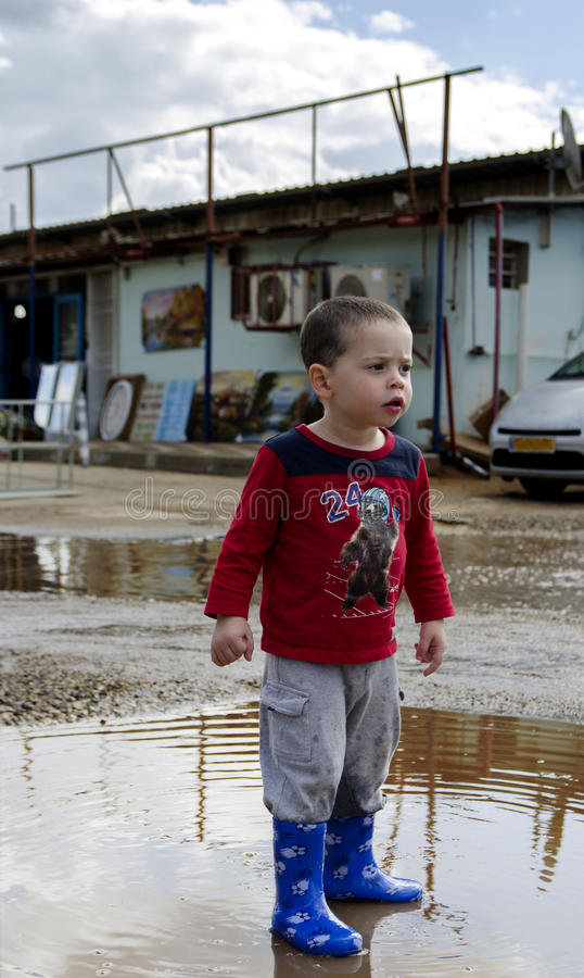 Toddler posing in a puddle with his new boots stock images