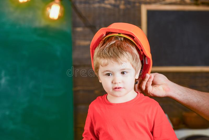 Toddler in protective hard hat, helmet at home in workshop. Carefully protect kid with helmet. Protection and safety stock photography