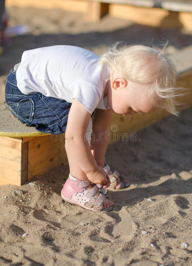 Toddler put on her shoes royalty free stock photo